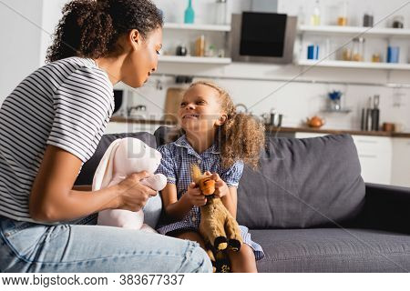 African American Nanny And Babysitter Holding Toys While Looking At Each Other In Kitchen