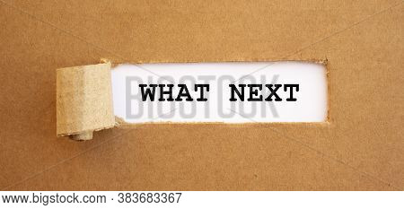 Text What Next Appearing Behind Torn Brown Paper.