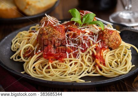 Spaghetti And Meatballs With Tomato Sauce And Parmesan Cheese On A Black Dinner Plate