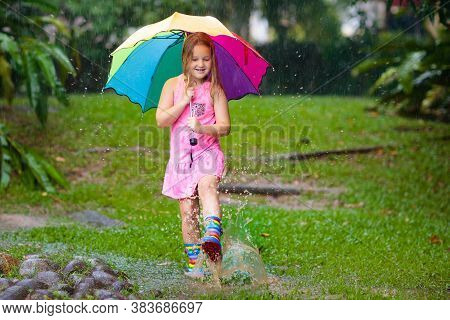 Kid Playing Out In The Rain. Children With Umbrella And Rain Boots Play Outdoors In Heavy Rain.