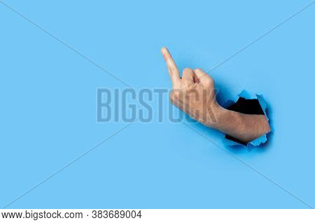 Hand Shows The Gesture Of The Middle Finger On A Blue Background. Offensive Gesture, Fuck Off, Leave