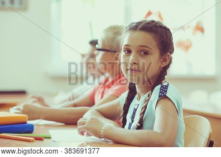 Portrait Of Pretty Hispanic Schoolgirl  Studing In Classroom During Lesson At Primary School