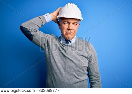 Middle age handsome grey-haired engineer man wearing safety helmet over blue background confuse and wonder about question. Uncertain with doubt, thinking with hand on head. Pensive concept.