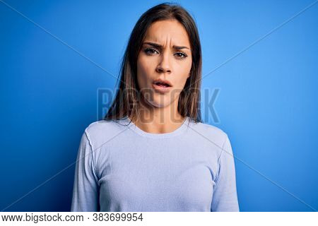 Young beautiful brunette woman wearing casual sweater standing over blue background In shock face, looking skeptical and sarcastic, surprised with open mouth