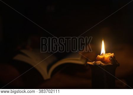 Reading A Book In The Dark By Candlelight