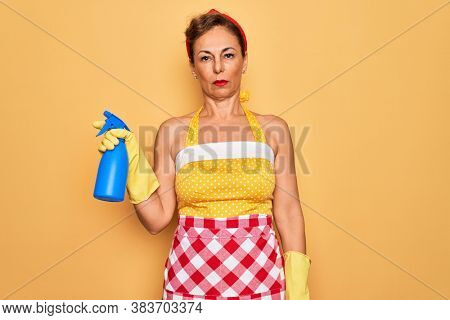 Middle age senior housewife pin up woman wearing 50s style retro dress cleaning using spray with a confident expression on smart face thinking serious