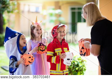 Kids Trick Or Treat In Halloween Costume. Children In Colorful Dress Up With Candy Bucket On Suburba