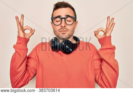 Young handsome man listening to music using headphones over isolated white background relax and smiling with eyes closed doing meditation gesture with fingers. Yoga concept.