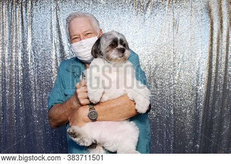 Photo Booth. A  Caucasian Man wears a Anti-Covid 19 Face Mask as he poses with his dog for photos in a Photo Booth with a silver sequin background.