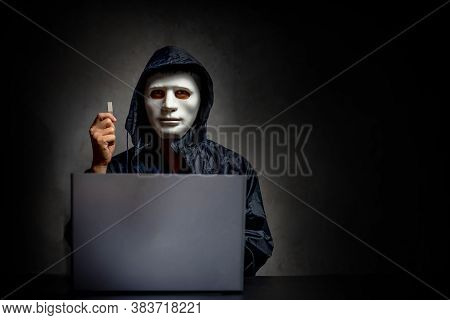 Male Hacker Hidden Face With The Mask And Hoodie. Obscured Dark Face Holds A Usb Flash Drive In His