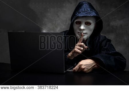 Male Hacker Hidden Face With The Mask And Hoodie. Obscured Dark Face Making Silence Gesture Try To H