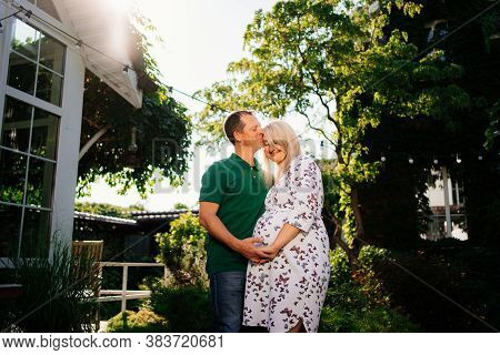 Pregnant Woman With A Man In The Back Garden Of The House. Happy Family Waiting For A Baby. Long-awa