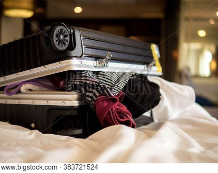 Travel And Vacation Concept, Packing A Lot Of Clothes And Stuff Into Suitcase On Bed Prepare For Tra