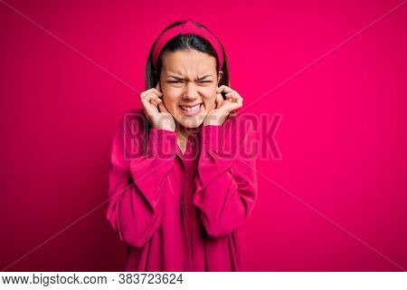 Young beautiful brunette girl wearing casual shirt standing over isolated pink background covering ears with fingers with annoyed expression for the noise of loud music. Deaf concept.