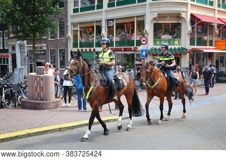 Amsterdam, Netherlands - July 10, 2017: Equestrian Police Officers Patrol Amsterdam. Police (politie