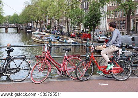 Amsterdam, Netherlands - July 10, 2017: Cyclist Crosses Herengracht Canal In Amsterdam, Netherlands.