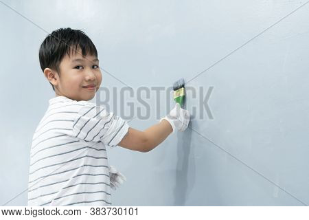 Asian Boy Using Paint Roller Paint The White Walls To Gray.children Practice Their Skills By Helping