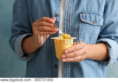 Woman Hold Plastic Cup Of Sour Cream Yogurt And Spoon Against Blue Background