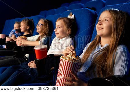 Selective Focus Of Smiling Little Girl Holding Popcorn Bucket, Sitting With Laughing Friends In Comf