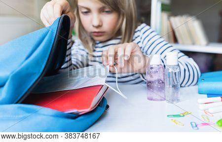 Little Girl Packing Blue Backpack In Kids's Room. Face Mask, Bottle Of Sanitizer, Stationery, Pens,