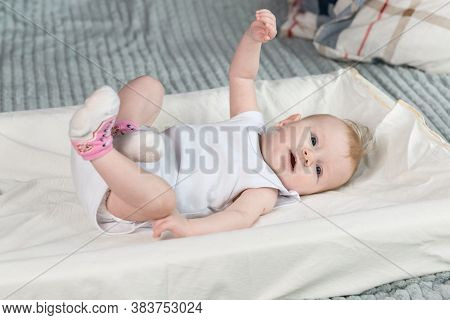 A Four-month-old Baby In White Clothes Is Lying On His Back. The Arms And Legs Are Raised Up. The Ba