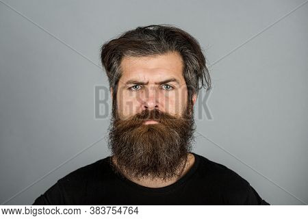 Portrait Of Confident Serious Man Has Beard And Mustache, Looks Seriously, Isolated. Hipster Guy Wit