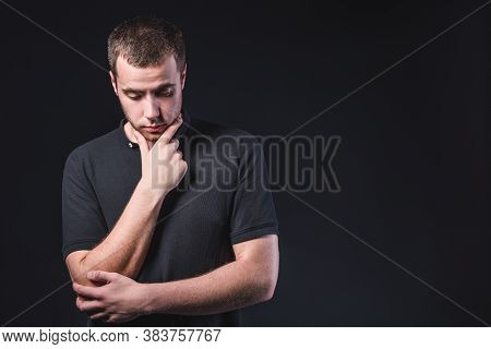 Portrait Of An Emotional Handsome Young Man, On A Black Background In The Studio, Who Stands In A Br