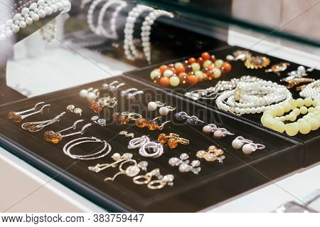 Behind Glass Jewelry On A Black Box. Earrings, Bracelets, Ring. Yellow And Brown Stones. Diamonds, T