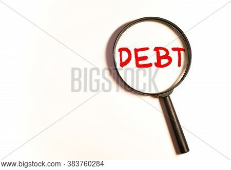 A Magnifying Glass Looks At A Bag With The Inscription Debt. Unclosed Obligations Between Two Person