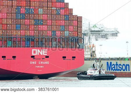 Oakland, Ca - July 31, 2020: Tugboat Independence At The Stern Of Cargo Ship One Crane, Assisting Th