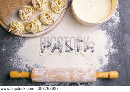 Homemade Uncooked Pasta Tagliatelle And Rocking For The Dough On Black Background. Making Fresh Ital