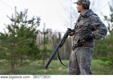 The Hunter Loads The Shotgun And Removes The Cartridge From The Cartridge Belt In A Clearing In The
