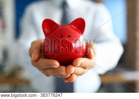 Close-up Of Man Holding Bright Red Piggy Bank. Persons Hand With Container For Saving Money. Cash Fo
