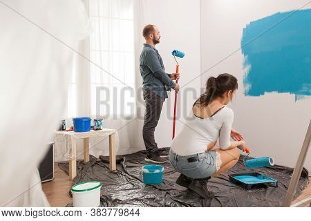 Married Couple Painting Apartment Wall With Roller During Home Renovation Using Blue Paint. Apartmen