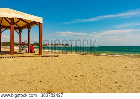 Woman With Bicycle Relaxing On Quitapellejos Beach, Andalucia Region In Spain. Activity On Holidays