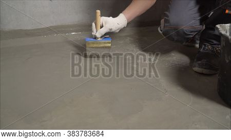 The Process Of Priming The Floor With A Solution. Waterproofing A Concrete Floor. Repair Cracked Flo