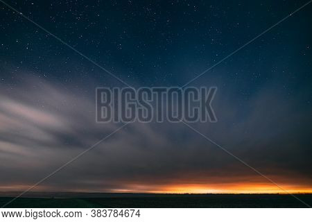 Night Starry Sky With Glowing Stars Above Countryside Landscape. Light Cloudiness Overcast Above Rur