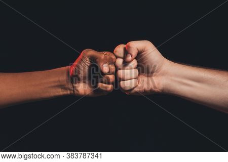 Black Lives Matter. Races Fights. African Caucasian Male Fists Bumping Isolated On Dark Copy Space.