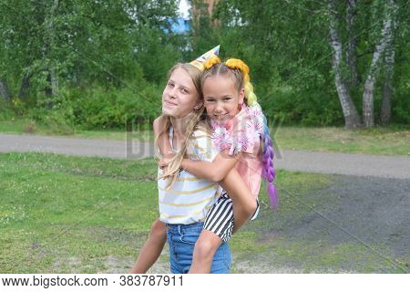 Beautiful Girls Having Fun Celebrating Birthday. Teenager Girl Lifting Her Friend On A Back, A Girl