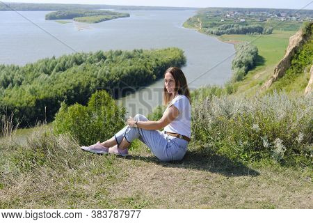 Beautiful Middle Age Woman Sitting Over High River Bank. Tranquil Place For Relaxation And Calm. Min