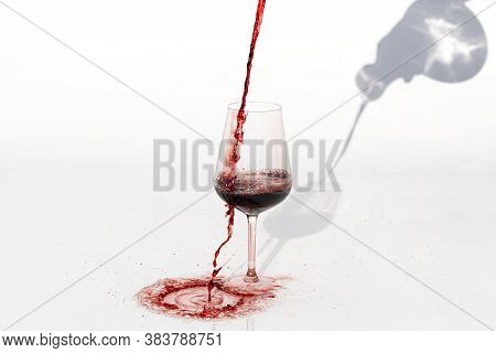Sommelier Pours Red Wine From Decanter To Wineglass On White Background. Spilling Red Wine Past The