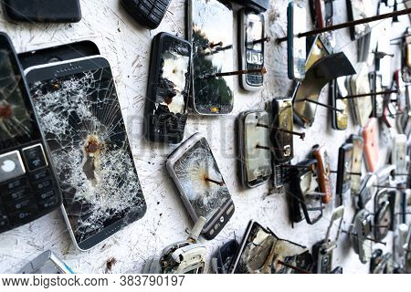 A Blurry Background Of Broken Phones Nailed To The Wall.