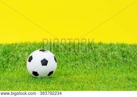 Miniature Toy Soccer Ball Lies On Green Grass Of Artificial Turf Of Football Field, Yellow Backgroun
