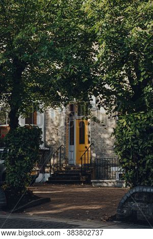 London, Uk - August 20, 2020: Bright Yellow Front Door Of A Traditional Terraced House In Crouch End