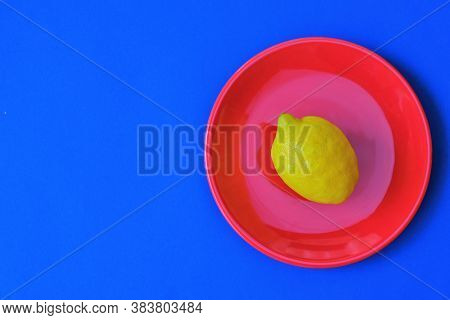 Lemon Fruit In A Minimal Style. Bright Yellow Lemon In A Red Round Plate On A Blue Background.graphi