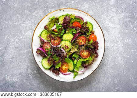 Healthy Vegetable Salad Of Cherry Tomatoes, Cucumber Slices, Green And Purple Lettuce Leaves, Onions