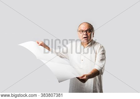 Indian Retired Senior Or Old Man Reading Book Or Newspaper