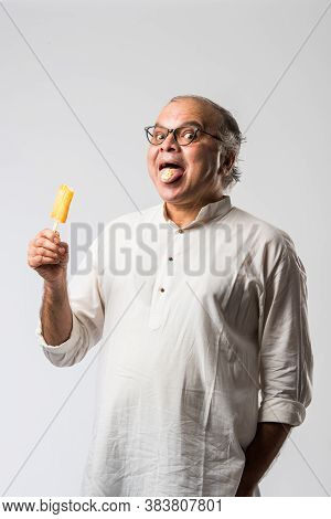 Retired Indian Old Man Eating Ice Cream, Standing Icolated Against White Background