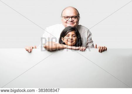 Indian Asian Cute Little Girl Pointing At Blank White Board With Grandpa Or Grandfather