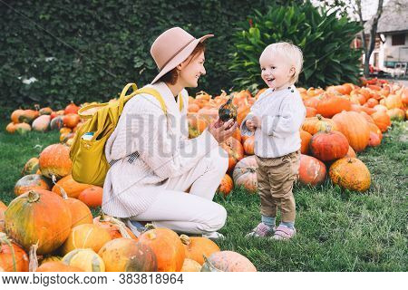 Happy Mother And Child At Pumpkin Patch Outdoors.